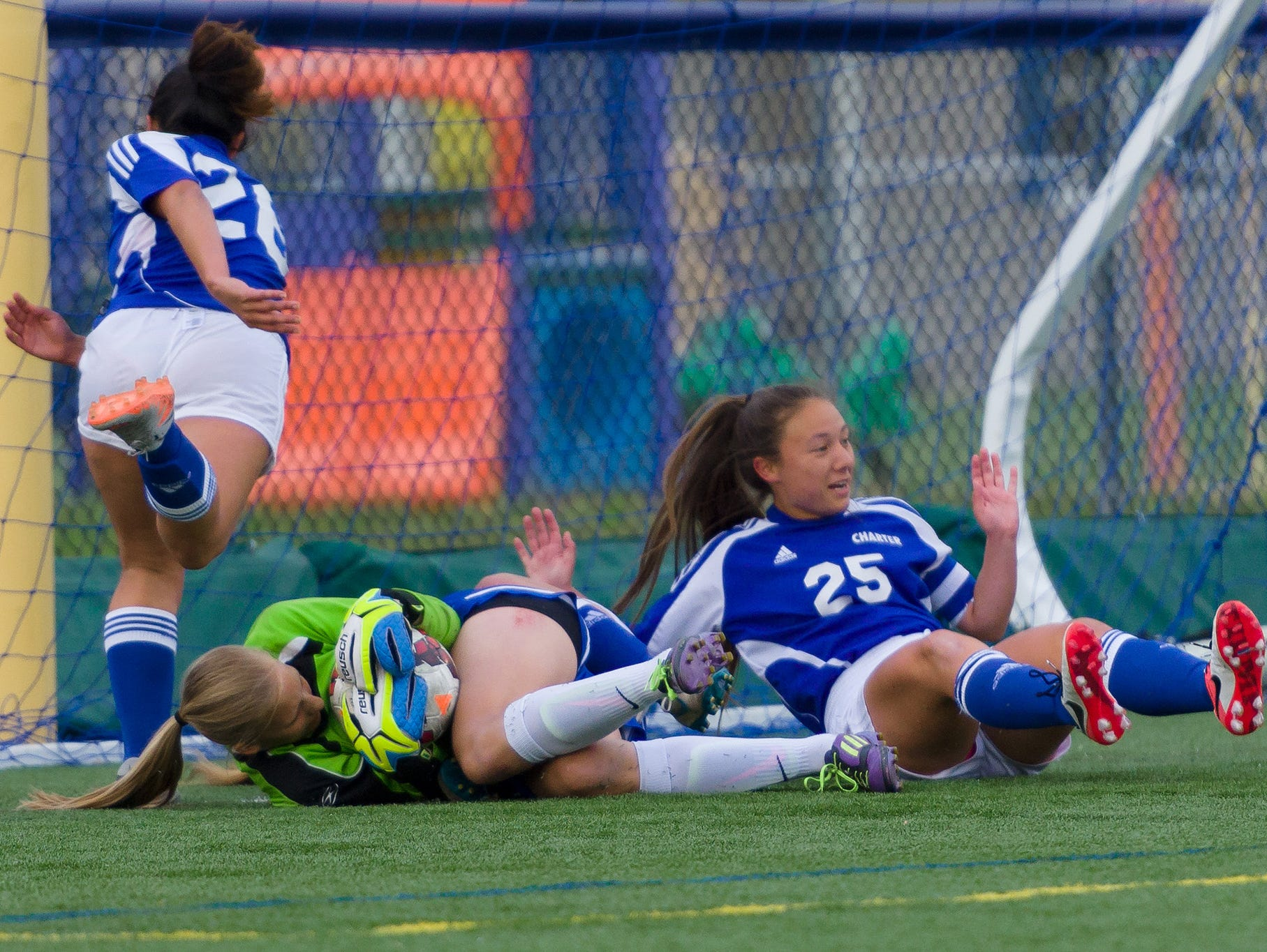 Taylor Wolf (9) makes a save for Middletown as Charter;s Felicia Flores (26) and Alli Munro (25) avoid contacting her in a Charter at Middletown girls soccer game on Wednesday.