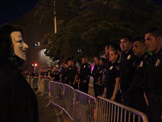 A protester stands in front of police while wearing