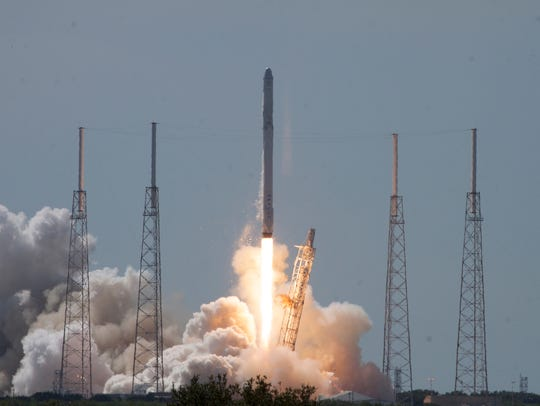 A SpaceX Falcon 9 rocket and Dragon capsule lifted