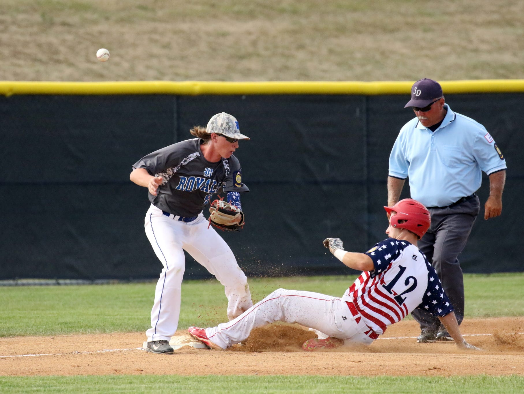 Drake Messinger of Rapid City Post 22 slides into third as the ball gets past Trevor Schaller of Renner 307 during Sunday's Championship game in Sioux Falls.