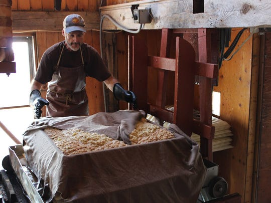 James Bove of Chapin Orchard folds a cloth around ground
