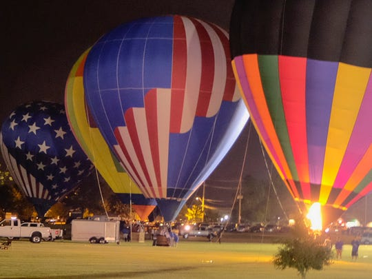 Hot air balloons are lit up in the evening by the flames from the propane burners.