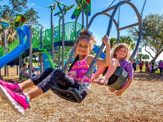 University Park Elementary students try out the new playground at Riverview Park in Melbourne.