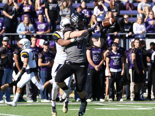 Josh Angulo of USF hauls in a pass as Jonathan Johnson of Concordia-SP defends during Saturday's game in Sioux Falls.