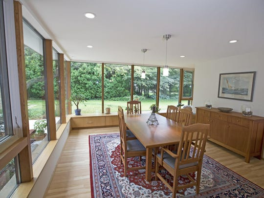 The dining room of Ted and Beth Durant's Fox Point home has floor-to-ceiling windows on two sides, allowing diners a direct view of the front yard and courtyard.