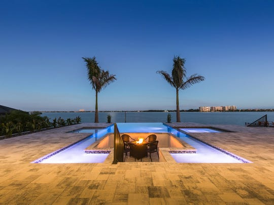 On the lanai is an infinity-edge pool and a spa and a fire pit area that is nestled below the decking with views of the Caloosahatchee River.