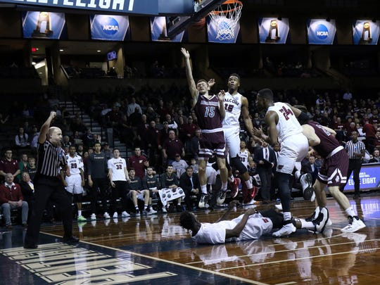Brent Bach of Bellarmine draws a blocking foul as he puts up a shot between several Fairmont State defenders during Thursday's DII Championship semifinal game in Sioux Falls.