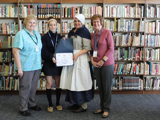 Immaculata student and Chapter winner Carmela Streicher of Clinton Township, pictured here with her History teacher Joann Fantina, DAR representative Erica White, and Principal Jean Kline, put a GPS system into the hands of Columbus and his navigators.