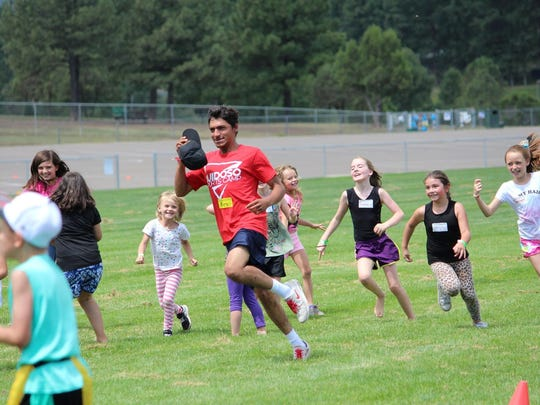 Adults try to keep pace with children in the field at Sports Camp.