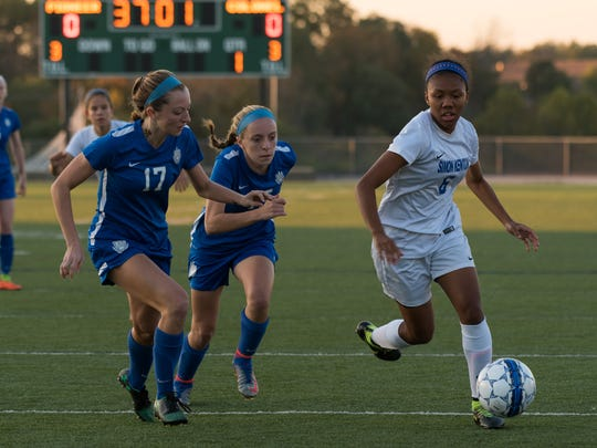 Sophomore midfielder Cayla Coleman, right, attacks down the side against two defenders