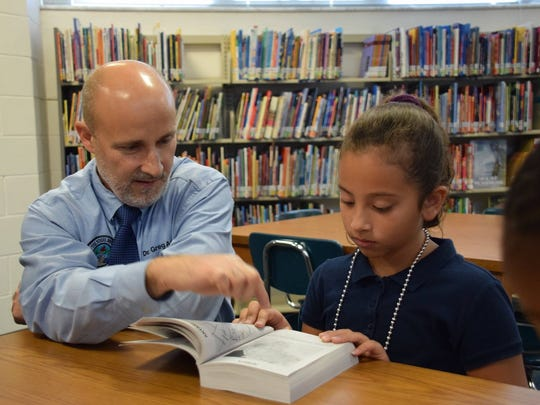 Superintendent Greg Adkins shows a student how to use