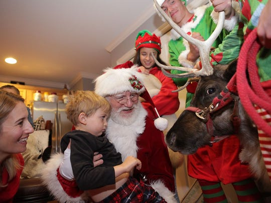 Santa Claus holds Chad Carr in his arms, showing him the reindeer that came for his final Christmas celebration on Nov. 14, 2015. Chad's mother, Tammi Carr, and an elf look on.