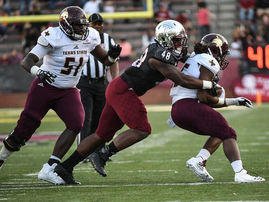 Texas State Bobcats running back Anthony D. Taylor (25) is tackled by Troy Trojans defensive tackle Marcus Webb (48) during a football game between the Troy Trojans and the Texas State Bobcats on Nov. 24, 2017, at Veterans Memorial Stadium in Troy.