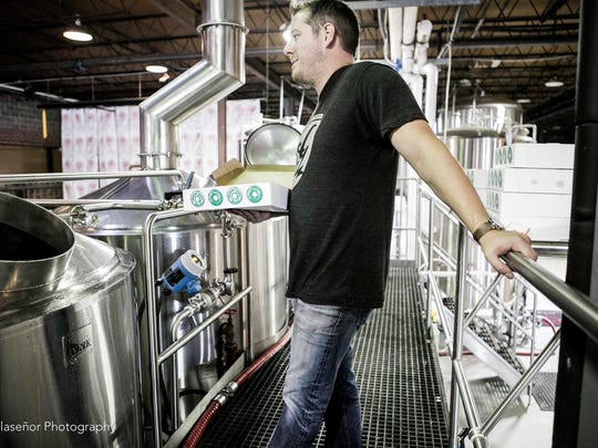 Andrew Nations, president of Great Raft Brewing, holds