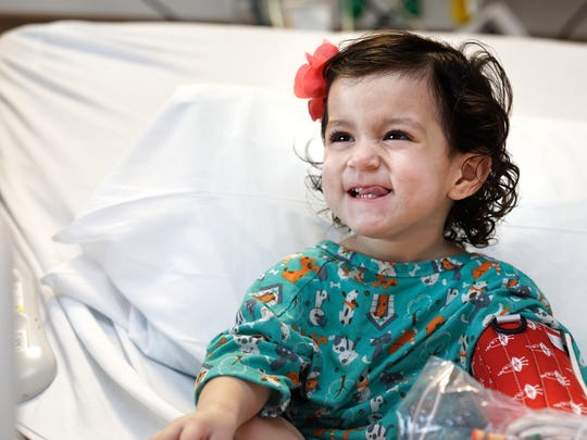 Isabella Soto smiles while relaxing at Johns Hopkins All Children's Hospital in St. Petersburg. The daughter of Marco Soto and Vivianne Gutierrez, Isabella, not yet 2, will require more surgeries to heal after she swallowed a button battery, found in a number of children's toys.