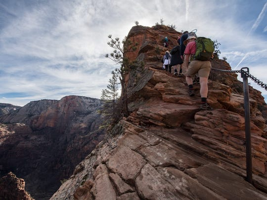Hikers use a chain to help navigate the peak of Angels Landing in Zion National Park Monday March 12, 2018. The top of the trail is often congested, with hikers moving past each other on narrow pathways.