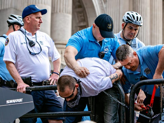 Security works to unchain a protester at a rally for John Fetterman with Bernie Sanders at Philadelphia City Hall.