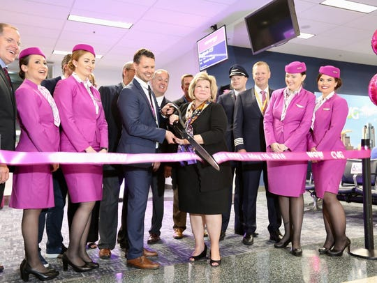 CVG and WOW Air representatives cut a ribbon at gate