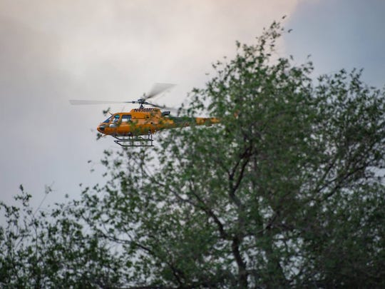 An emergency personnel helicopter flies over the Soldier Canyon Fire in Mescalero.