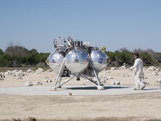 On Feb. 12, 2014, a technician checked NASA's Project Morpheus prototype lander after it landed on a pad inside a hazard field simulating the lunar surface at the north end of Kennedy Space Center's former Shuttle Landing Facility.