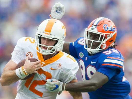 Tennessee quarterback Quinten Dormady (12) runs the ball as Florida defensive lineman Jachai Polite (99) goes for the tackle during the Tennessee Volunteers vs. Florida Gators game at Ben Hill Griffin Stadium in Gainesville, Florida on Saturday, September 16, 2017.