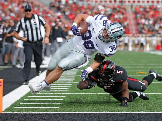 Kansas State's Winston Dimel (38) scores a touchdown past Texas Tech's Octavious Morgan (5) that was called back after a targeting penalty, during an NCAA college football game Saturday, Nov. 4, 2017, in Lubbock, Texas. (Brad Tollefson/Lubbock Avalanche-Journal via AP)