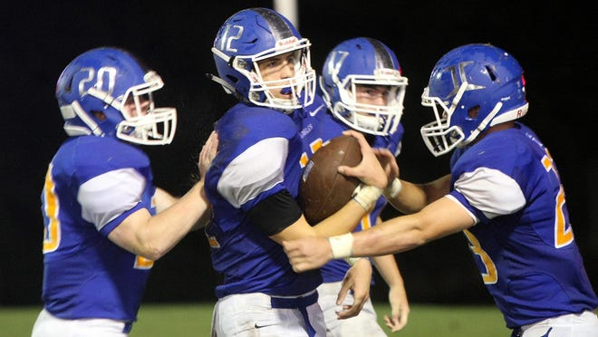 Jackson Christian's Gunnar Lewis (12) is congratulated by Luke Robertson (20), Hayden Love (17) and Ethan Anderson (23) after making an interception versus Donelson Christian Academy.