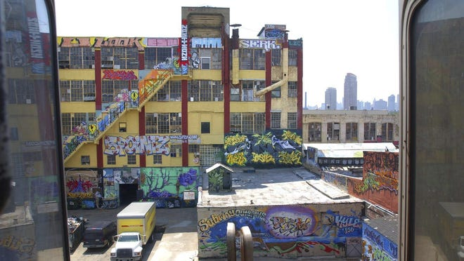 """In this July 8, 2004 file photo, a warehouse building known as """"5 Pointz"""" is shown with graffiti work from various artists from around the world, is visible between cars of an elevated subway train in the Queens, N.Y. Four years after the graffiti-covered warehouse was whitewashed, a jury will decide whether the street art deserved protection under the law. (AP Photo/Frank Franklin, File)"""