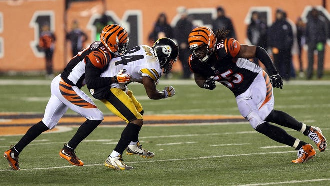 Vontaze Burfict (55) hits Antonio Brown during the fourth quarter of a 2015 AFC wild-card playoff game at Paul Brown Stadium. Burfict was called for a personal foul on the play.