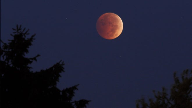 A lunar eclipse appears above Erie, Pa. at about 6:45 a.m. on Wednesday morning, Oct. 8, 2014.  The moon appears orange or red, the result of sunlight scattering off Earth's atmosphere. This is known as the blood moon.  (AP Photo/Erie Times-News, Christopher Millette)