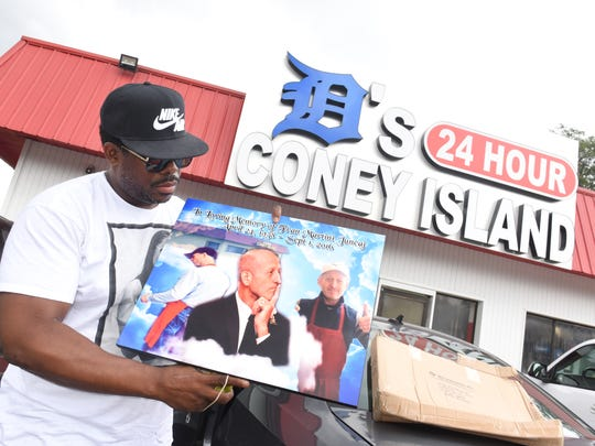 DeShawn Reed holds a photograph of former owner Frank Juncaj outside D's Coney Island in Detroit on July 31, 2018, Reed has purchased the Coney Island after being released 9 years ago for being wrongfully incarcerated. Reed, is  reopening a coney island in his community after the former owner Frank Juncaj was shot and killed in 2016.