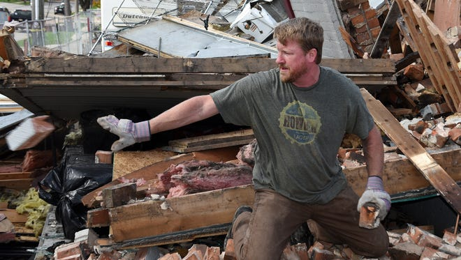Corry Bala, co-owner of the South Lyon Hotel, tosses some bricks destined to be souvenirs - or part of the new restaurant's bar, into a pile on Oct. 17 as the structure is torn down. The structure, from 1867, was severely damaged by fire this in June.