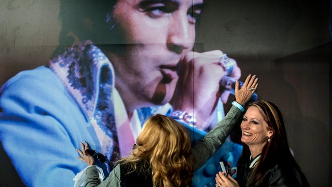 """Shelley Dorazio, left, embraces a picture of Elvis Presley while Jenny Furr laughs inside the new Elvis Presley's Memphis installation at Graceland on March 2, 2017. Elvis Presley Enterprises opened 200,000 square feet of new exhibits, museums and performance space behind Graceland Plaza, the longtime hub of mansion tours. """"He's mine,"""" Dorazio said. """"I'm not sharing him."""""""
