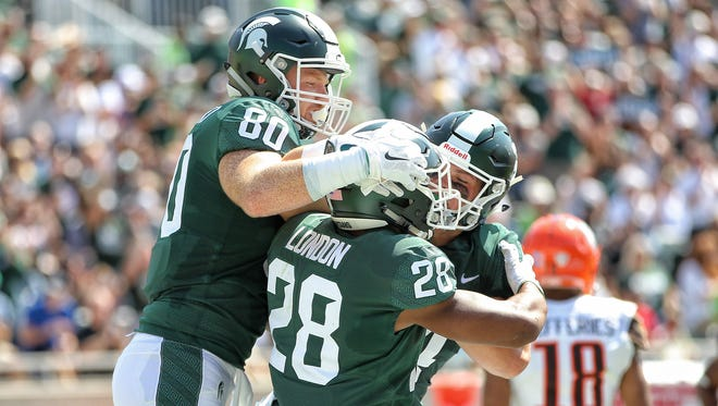 Michigan State Spartans tight end Matt Seybert (80) and Michigan State Spartans running back Madre London (28) celebrate a touchdown during the first quarter of a game against the Bowling Green Falcons at Spartan Stadium.