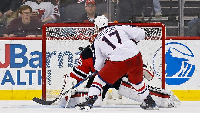 Columbus Blue Jackets center Brandon Dubinsky (17) scores on a penalty shot past Devils goalie Cory Schneider (35) during the second period on Sunday.