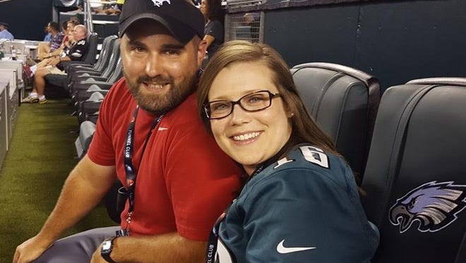 Susquehannock High School science teacher Laura Krotzer, right, sits with her husband, Jesse, at an Eagles game.