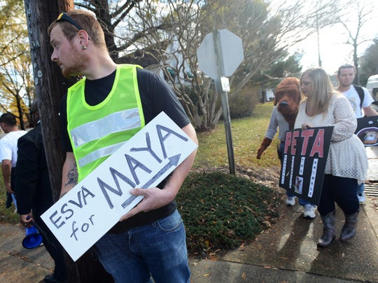 Brandon Smith holds a sign to direct traffic as protesters