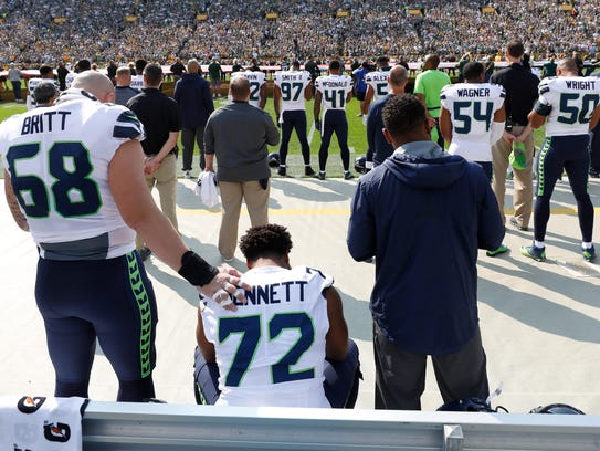 Seattle Seahawks' Michael Bennett remains seated on