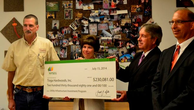 NYSEG officials presents a $230,000 check to Tioga Hardwoods President Kevin Gillette, left, on Tuesday.