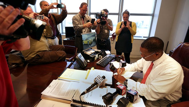 Detroit emergency manager Kevyn Orr signs Order #42 that gives all authority back to Detroit Mayor Mike Duggan and the Detroit City Council in front of reporters in his office at the Coleman A. Young Municipal Building in Detroit on Thursday.