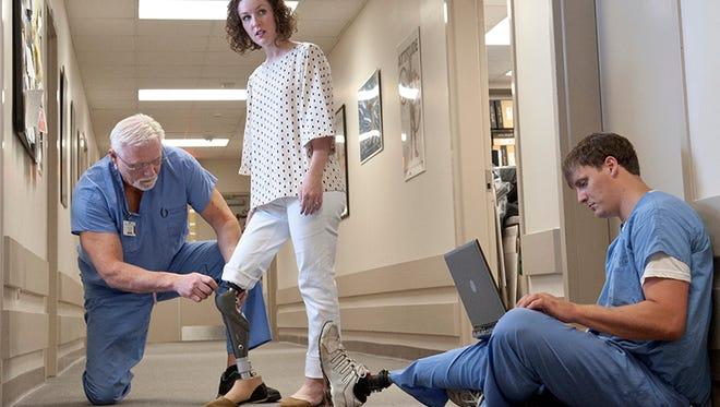 Rachel Gunalda (center) receives an adjustment to her prosthetic leg.