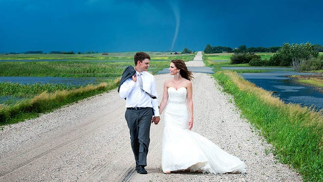 A wedding photographer in Canada caught a tornado in the background during an outdoor wedding photo shoot