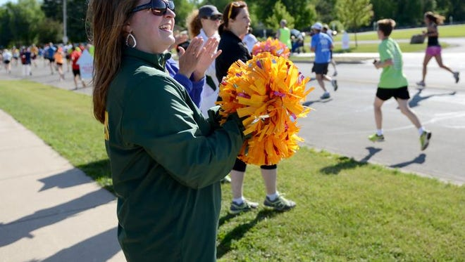 Amanda Wery, De Pere, cheers on runners along Libal Street during the 2014 Bellin Run, Saturday, June 14, 2014.