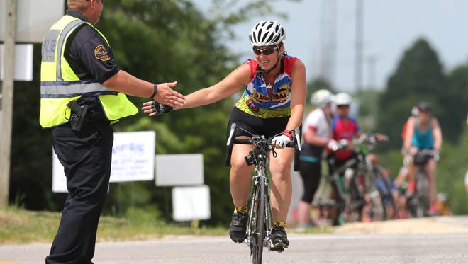 A rider offers a Cedar Falls police officer a high five as a thank you for his service as she rolls into town during RAGBRAI on Wednesday, July 22, 2015.