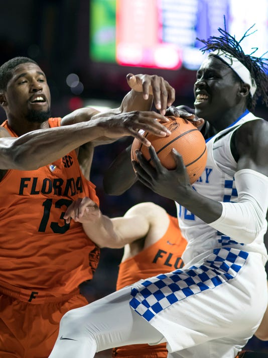 Florida forward Kevarrius Hayes (13) and Kentucky forward Wenyen Gabriel (32) fight for a loose ball during the second half of an NCAA college basketball game in Gainesville, Fla., Saturday, March 3, 2018. Florida won 80-67. (AP Photo/Ron Irby)
