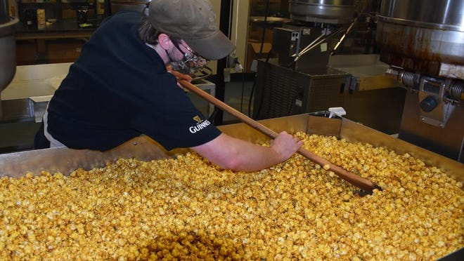 Inpopnito employee Matt Jean uses a large wooden spoon to disbuse spices over the popcorn at the Fall River business.