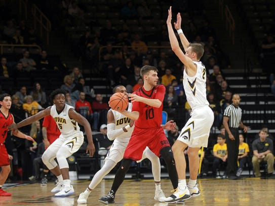 Southern Utah's Jacob Calloway is guarded by Iowa's
