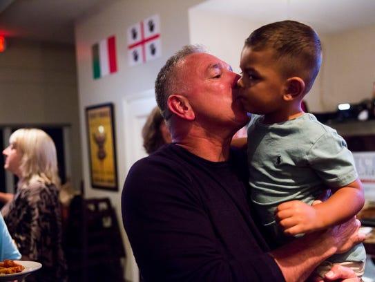 Mitch Norgart kisses his grandson Kamden Wilson, 2,