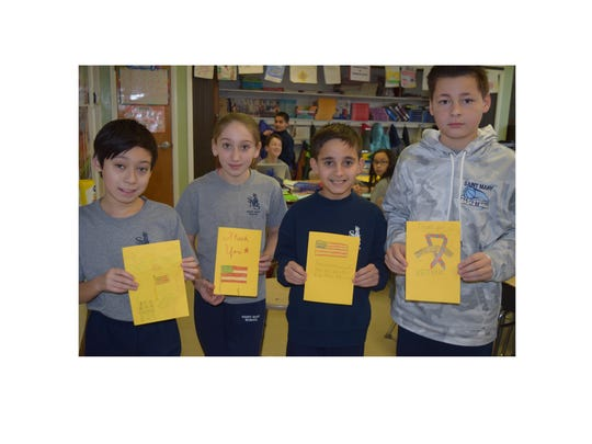 Sean Robertson, Ava Felice, Jeffrey Cullis and Nicholas Zane display cards they created for residents of the New Jersey Veterans Memorial Home in Vineland.