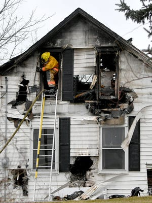 A Crestline firefighter exits a window of a home at 4851 old Lincoln Highway just east of Crestline on Tuesday morning. The fire started around 4:30 A.M. and two people were transported to hospital with smoke inhalation.